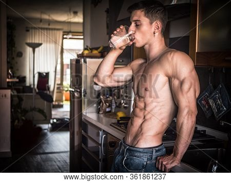 Young Shirtless Man In Kitchen Drinking Water