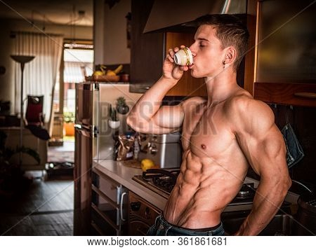 Muscular Topless Man Drinking Espresso Coffee In Kitchen