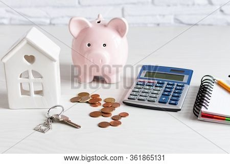 Piggy Coin Bank, Calculator And House Model On White Wooden Background. Savings For Buying House Con