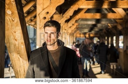 Young Man Standing On Wooden Footbridge In Switzerland While Looking Away