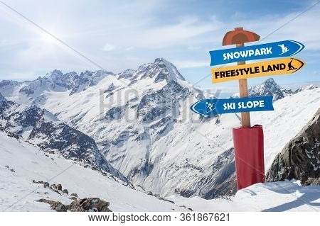 Road Sign In The Snow Show The Direction Of Snow Park, Freestyle Land And Ski Slope. Winter Scenic I