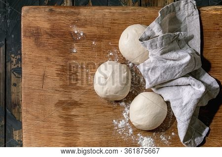 Dough For Pizza Cooking. Three Balls Of Fresh Homemade Wheat Dough Under Linen Cloth On Wooden Table