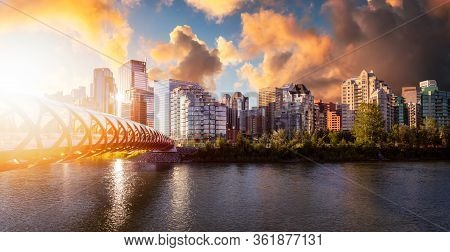 Peace Bridge Across Bow River With Modern City Buildings In Background During A Vibrant Summer Sunri