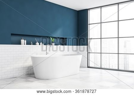 Corner Of Modern Bathroom With Blue And White Brick Walls, Tiled Floor, Comfortable White Bathtub An