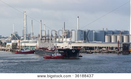 Two Tugboats Manoeuvring An Oil Tanker In The Dutch Harbor Of Rotterdam