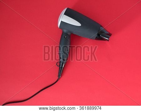Black Hair Dryer Isolated On Red Background. Electric Hair Dryer