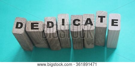 Word Dedicate On A Row Of Wooden Blocks. Devotion Dedication Love Concept