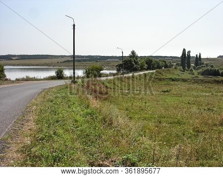 A Rural Road Runs Over A Dam Across A Pond.