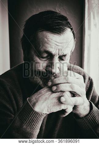 Sad pensive elderly man at home by the window. Coronavirus Quarantine Isolation Concept