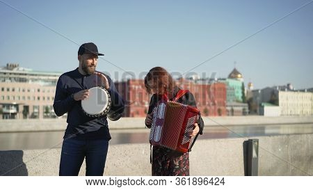 A Street Musician Plays Tom-tom On A Drum. Street Musicians Play On The Street On A Drum And Accordi