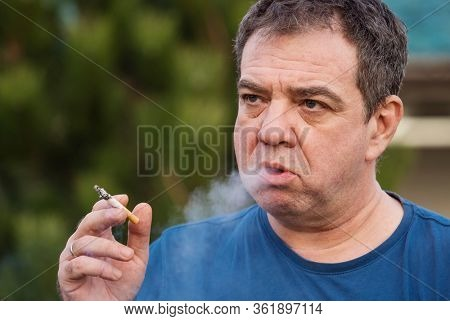 Adult man smokes in the park