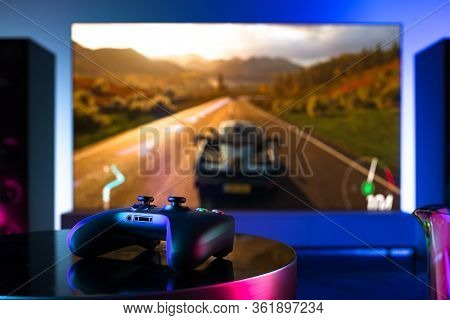 Wireless Joystick On Foreground, Tv Set With Racing Video Game On Background. 3d Rendering.
