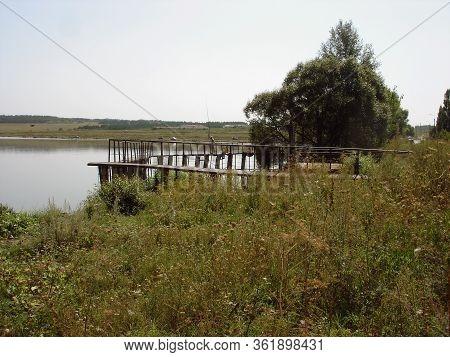 Flood Spillway Of A Rural Pond On An Earthen Dam. Fishermen Catch Fish From The Flood Spillway Of Th