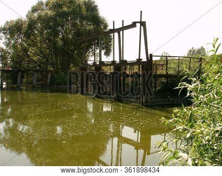 Flood Spillway Of A Rural Pond On An Earthen Dam. The Flood Spillway Of The Pond Dam Is Equipped Wit