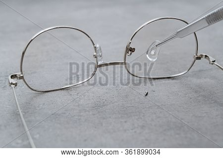 Closeup Of Professional Repairing Of Eyeglasses With Ophthalmology Instrument In Clinic Office And O