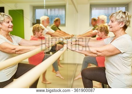 Senior group doing physiotherapy exercise on the ballet bar in front of the mirror