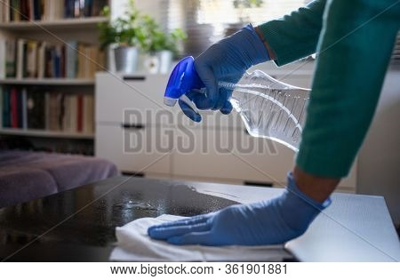 surface home cleaning spraying antibacterial sanitizing spray bottle disinfecting against COVID-19 spreading wearing medical blue gloves. Sanitize surfaces prevention in hospitals and public spaces.