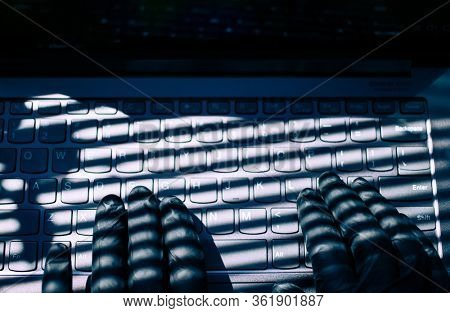 hand typing on keyboard with black gloves  data protection online fraud hacker