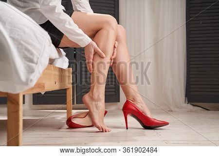 Woman is massaging tired legs in stilettos.