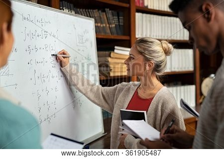 Young woman solving mathematics problem on whiteboard. College student solving algebra equation on white board in library with students. Girl trying to understand mathematics problem during lesson.