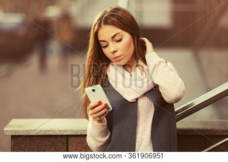 Young fashion woman using cell phone on city street Stylish female model in gray sleeveless coat and light pink sweater