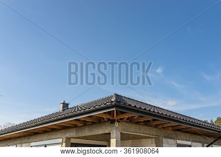 The Roof Of A Single-family House Covered With A New Ceramic Tile In Anthracite Against The Blue Sky