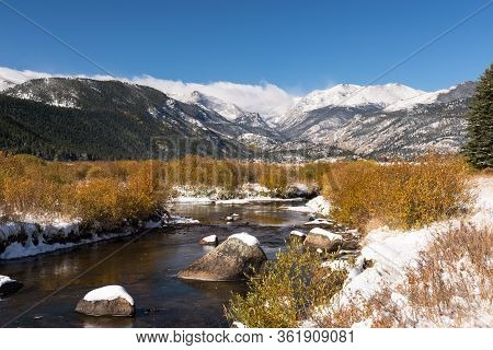 A Stream Flows Through Moraine Park With High Mountain Peaks Rising Above The Valley In Rocky Mounta