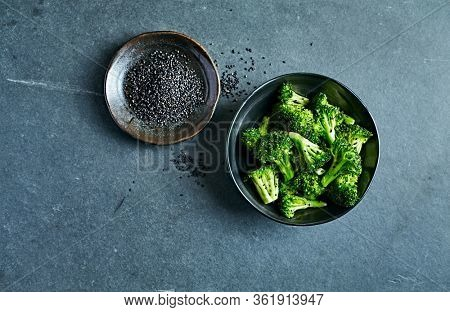 Stir fry broccoli with black sesame in a black ceramic bowl. Healthy cooking. Copy space