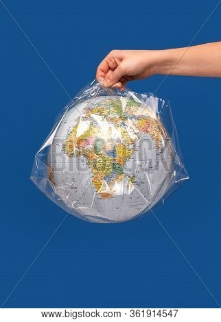 Hand Holding A World Globe Wrapped In Plastic.