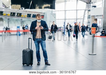 Horizontal Shot Of Man Poses In Crowded Airport, Uses Cell Phone, Checks Time Of Flight Online, Stan