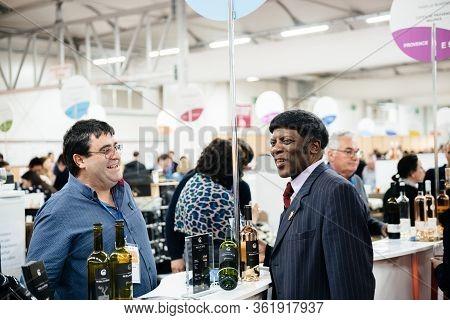 Strasbourg, France - Feb 16, 2020: Black Ethnicity Sommelier Talking With Winemaker At The Vignerons