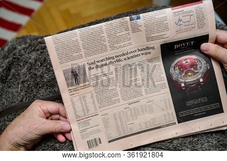 Paris, France - Feb 19, 2020: Pov Of Senior Hands Holding Latest Financial Times Newspaper Featuring