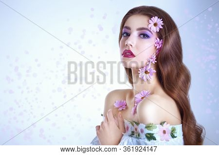 Portrait of a beautiful brunette girl with soft lilac flowers of chrysanthemums on her face and body on a white background. Beauty, spa and cosmetics concept. Copy space.