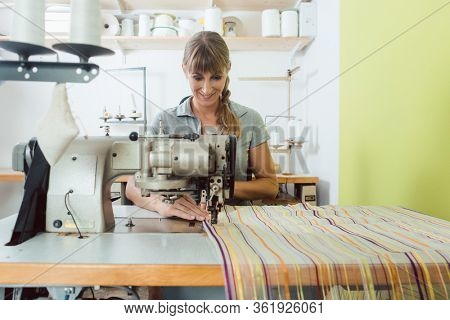 Seamstress sews colorful decorative fabric on sewing machine in a tailor's shop