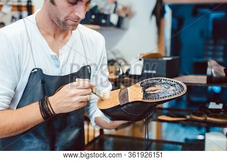 Shoemaker putting glue on sole of a shoe to fix
