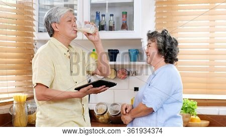 Senior Couple At Home, Old Asian Man Drinking Milk At Kitchen Standing With Old Woman, Elderly Asia