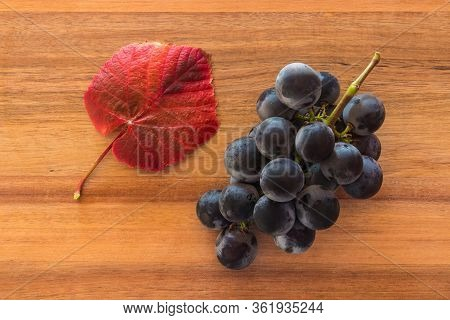 Bunch Of Ripe Cabernet Sauvignon Grapes With Red Leaf On Wooden Chopping Board