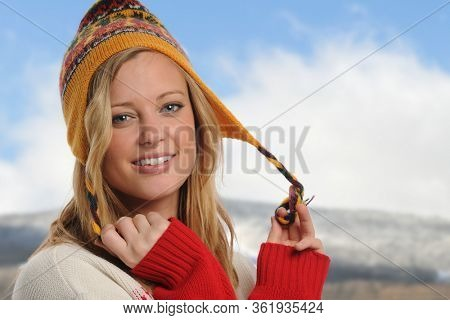 Pretty blond girl wearing a hat outdoors during winter