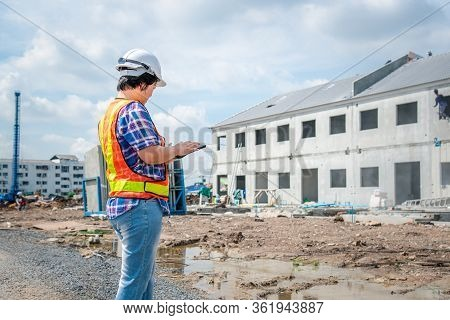 Asian Woman Civil Construction Engineer Worker Or Architect With Helmet And Safety Vest Working And