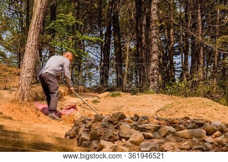 Daejeon, South Korea; April 16, 2020: Unidentified Man Digging In Ground With Garden Hoe Near Fresh