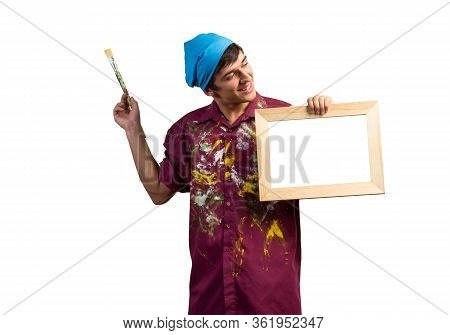 Young Handsome Painter Artist Holding Paintbrush And Blank Canvas In Frame. Portrait Of Happy Painte