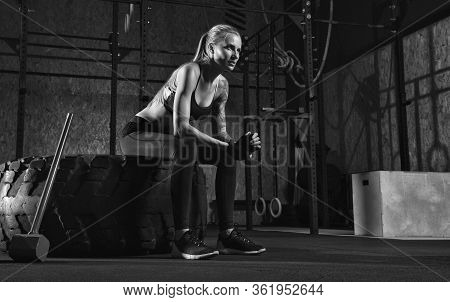 Fitness Woman Resting After Sledgehammer Workout At Gym. Fit Attractive Blonde Girl Taking Break Aft