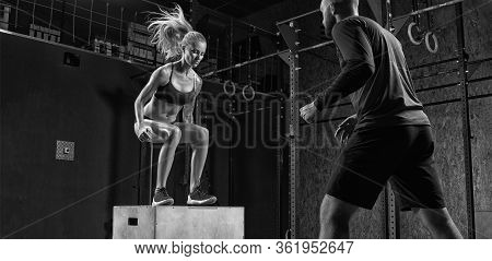 Fitness Woman Doing A Box Jump At The Gym With The Help Of A Personal Trainer In A Modern Gym Traine