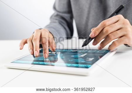 Woman Using Tablet Computer For Stock Trading. Close-up Of Female Hands Touching Screen Of Tablet De