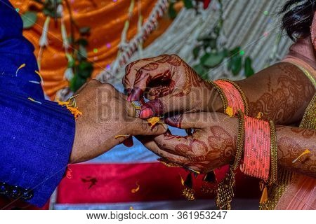 Engagement Ceremony; Indian Bride Putting A Wedding Engagement Ring On Finger Of Groom.