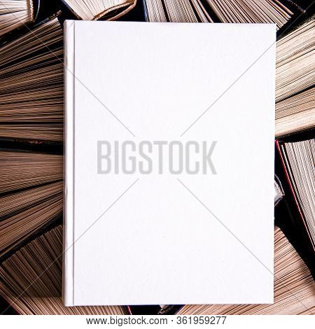 Mockup Of Closed Blank Square Book Rests On Open Old Multicolored Books