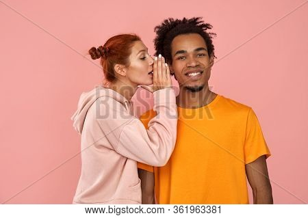 Young Ginger Woman Whispers Secret To Dark-skinned Boyfriend Who Has Cheerful Expression, Gossip Tog