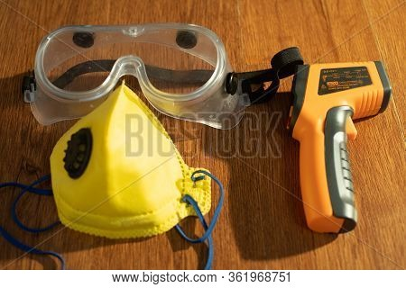 Protective Eyewear Yellow Mask With Outlet Valve And Infrared Contactless Thermometer On A Wooden Fl