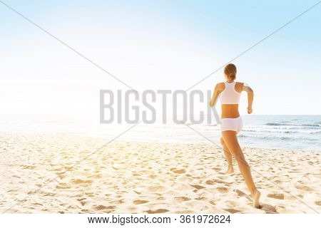 Woman Running On Sunny Sea Beach, Rear Back View, Girl In White Sexy Sport Clothes Jogging On Coast