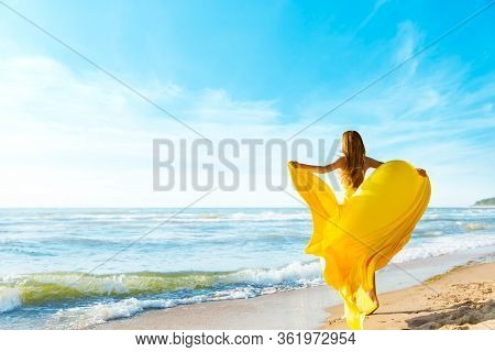 Woman On Sunny Sea Beach In Yellow Fluttering Dress, Fashion Model Back Rear View, Silk Cloth Waving